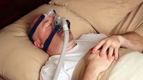Male patient asleep in bed with CPAP mask