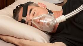 Male patient asleep on his side in bed with CPAP mask