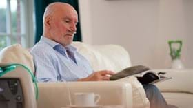 Elderly male patient with oxygen concentrator reading magazine at home